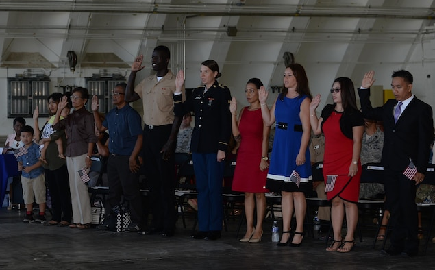 Prospective U.S. citizens take the Oath of Allegiance during a naturalization ceremony Nov. 23, 2016, on Andersen Air Force Base, Guam. The oath is recited during the ceremony, signifying an individual pledging their allegiance to the United States of America. (U.S. Air Force photo/Staff Sgt. Benjamin Gonsier)