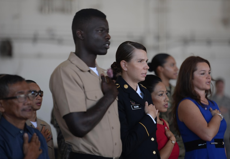 Newly naturalized U.S. citizens place their right hands over their heart as they recite the Pledge of Allegiance during a naturalization ceremony Nov. 23, 2016, on Andersen Air Force Base, Guam. A naturalization ceremony is the culmination serves of extensive application procedures, background investigations and successful completion of a citizenship test. (U.S. Air Force photo/Staff Sgt. Benjamin Gonsier)