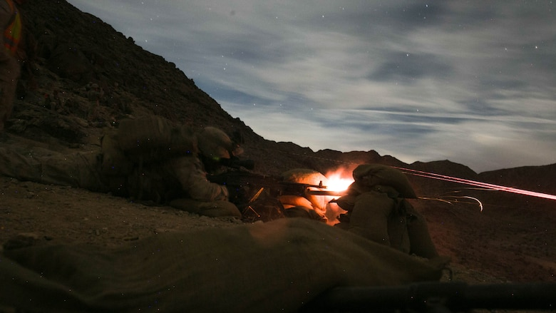Machine gunners with 1st Battalion, 7th Marine Regiment, fire an M240B medium machine gun at a target at Range 400 at Marine Corps Air Ground Combat Center, Twentynine Palms, California, during the unit's night-time combined arms live-fire exercise Nov. 16, 2016.