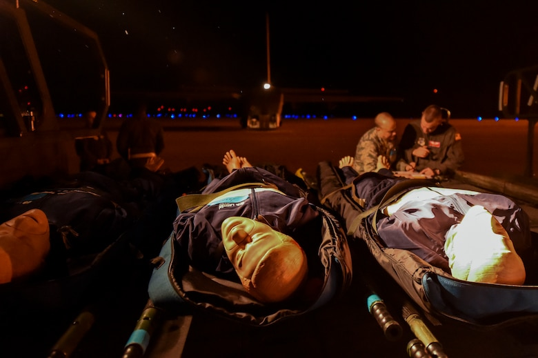 Simulated patients await evacuation as a team of medics from the 375th Aeromedical Evacuation Squadron discuss their plan to care for the patients during exercise Hurricane Greg, Nov. 8, 2016, at Alexandria, Louisiana.  The exercise was an example of how the U.S. Air Force provides support to local, state and federal authorities by performing a key role during crisis situations.  (U.S. Air Force Photo by Senior Airman Stephanie Serrano)
