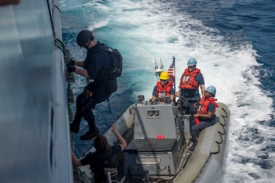 A USS McCampbell sailor disembarks the Royal Brunei Navy ship KDB Darussalam to board a rigid hull inflatable boat during a visit, board, search and seizure training exercise in the South China Sea, Nov. 17, 2016, as part of Cooperation Afloat Readiness and Training 2016. Navy photo by Petty Officer 2nd Class Christian Senyk