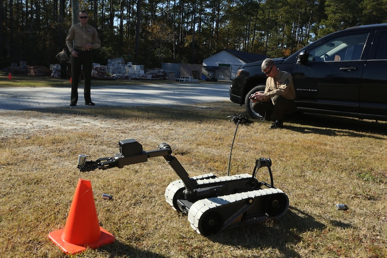 Staff Sgt. Steven M. Smith demonstrates some of capabilities of the 310 SUGV System robot by placing a battery in a cone while at the Swansboro High School in Swansboro, N.C., Nov. 17, 2016. The Marines came to help the school's robotics team by teaching them the basics and giving them a foundation in robotics. Smith is a team leader with Explosive Ordnance Disposal Company, 2nd Marine Logistics Group, at Camp Lejeune, N.C. (U.S. Marine Corps photo by Sgt. Clemente C. Garcia)