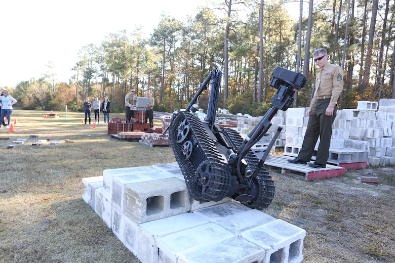 Staff Sgt. Justin S. Bryant shows a high school robotics team that the MK-2 Talon Robot can climb over objects during a demonstration at Swansboro High School in Swansboro, N.C., Nov. 17, 2016. The Marines have been coming to the school for the past three years to help inspire the student's creativity. The Marines are explosive ordnance disposal technicians with Explosive Ordnance Disposal Company, 2nd Marine Logistics Group. (U.S. Marine Corps photo by Sgt. Clemente C. Garcia)