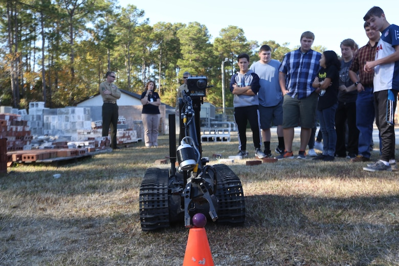 Marines remote control an MK-2 Talon robot during a demonstration for the Swansboro High School Robotics Team in Swansboro, N.C., Nov. 17, 2016. The Marines displayed three of their robots to students during a community relation event to inspire the students' creativity through robotics. The Marines are explosive ordnance disposal technicians with Explosive Ordnance Disposal Company, 2nd Marine Logistics Group. (U.S. Marine Corps photo by Sgt. Clemente C. Garcia)