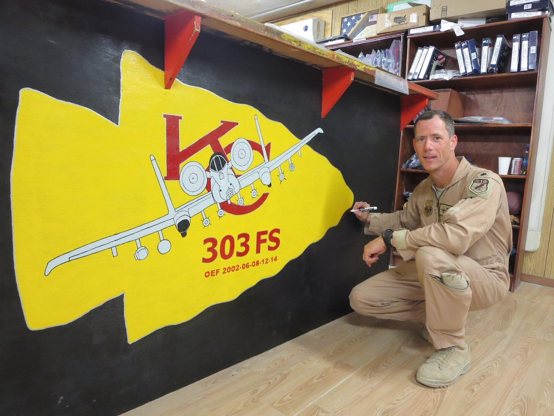 U.S. Air Force Lt. Col. John Marks smiles in front of his 303rd Fighter Squadron artwork at Bagram Air Base, Afghanistan, during Operation Enduring Freedom in 2014. The 303rd Fighter Squadron is attached to the 442d Fighter Wing, a Reserve wing located at Whiteman Air Force Base, Missouri. (Courtesy photo provide by Lt. Col. Marks)