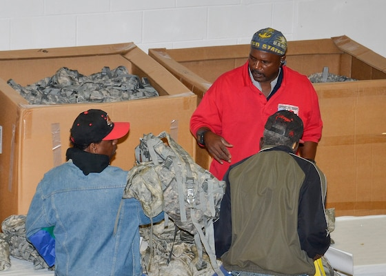 Navy veteran and volunteer, Steven Adams, hands out excess property from DLA Disposition Services to two homeless veterans in Battle Creek, Michigan.