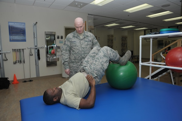 Tech. Sgt. Casey Berry, 359th Medical Operations Squadron Physical Therapy Flight chief, assists Airman 1st Class Gregory Jones on doing hamstring curls Nov.9, 2016 at Joint Base San Antonio-Randolph.  Physical therapists provide services that help restore function, improve mobility and relieve pain, therapists work closely with patients to help them heal and promote overall wellness.