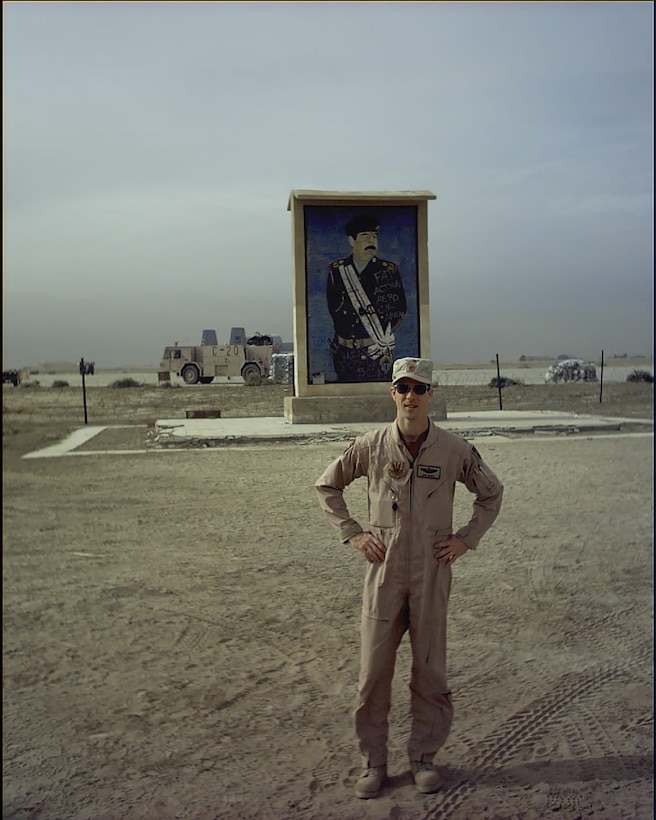 U.S. Air Force Maj. John Marks, 303rd Fighter Squadron pilot, poses in front of a Saddam sign near Tallil Air Base, Iraq, during Operation Iraqi Freedom in 2003. Other bases Marks has deployed to in support of Operation Iraqi Freedom include Ahmed Al Jaber AB, Kuwait, and Kirkuk AB, Iraq. (Courtesy photo provided by Lt. Col. Marks)
