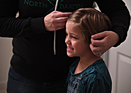 Shilo Willingham, 6, smiles into the mirror as her mom Kyla Willingham does her hair Nov. 21, 2016, on Grand forks Air Force Base, N.D. Kyla helps her kids get ready for school each day before she heads to the University of North Dakota where she is pursuing a Bachelor of Arts degree in History. (U.S. Air Force photo by Senior Airman Ryan Sparks)