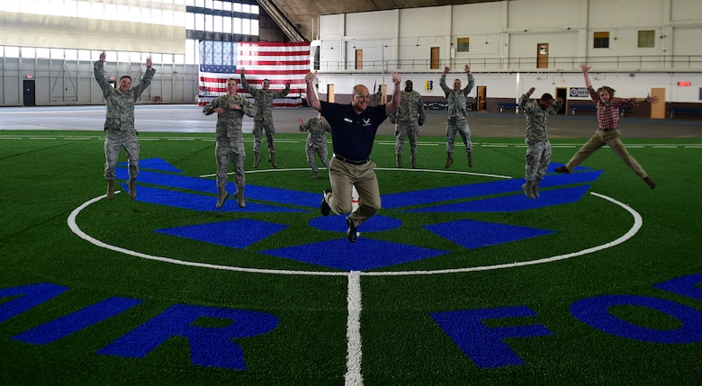 Members from the 28th Civil Engineer Squadron, 28th Contracting Squadron and 28th Force Support Squadron jump for joy inside the Pride Hangar at Ellsworth Air Force Base S.D., Nov. 21, 2016. Over the past month, members of the three squadrons completed a $249,000 renovation project and the facility is ready for use. (U.S. Air Force photo by Airman 1st Class James L. Miller)