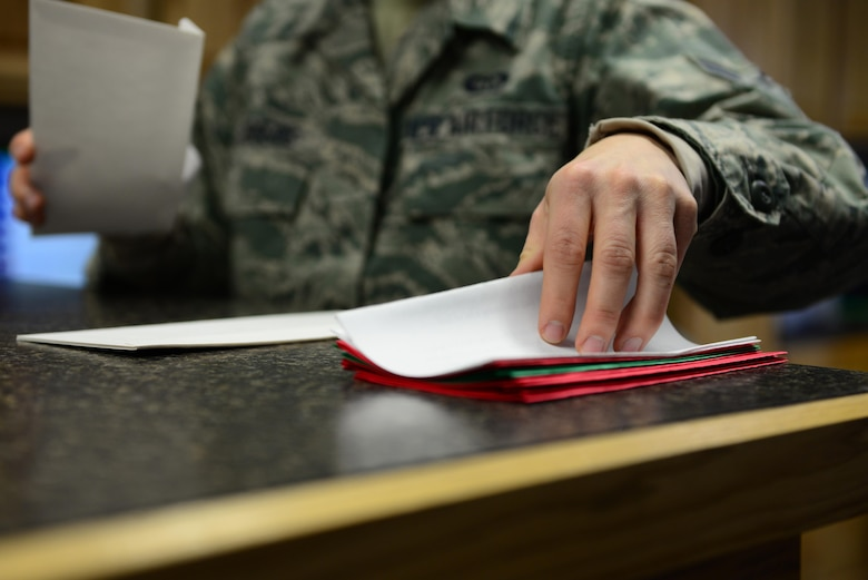 """U.S. Air Force Airman 1st Class Lisa Rogers, a 354th Operations Support Squadron weather forecaster apprentice, reaches for a letter Nov. 22, 2016, at Eielson Air Force Base, Alaska. Rogers and the weather flight send out hundreds of letters from Santa each year to children all around the world as part of the """"Santa's Mailbag"""" program which started more than 60 years ago. (U.S. Air Force photo by Airman 1st Class Cassandra Whitman)"""