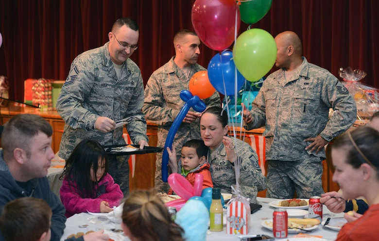 Senior Master Sgt. Jess Houk (left), 62nd Comptroller Squadron superintendent, serves food to Airmen and their families during the Hearts Apart dinner Nov. 17, 2016, at Joint Base Lewis-McChord, Wash. The dinner was attended by more than 50 Airmen and their families, who were provided a catered meal. (U.S. Air Force photo/Senior Airman Jacob Jimenez)