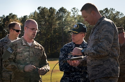 Tech. Sgt. Dwayne Ferugson, 628th Civil Engineer Squadron explosive ordnance disposal technician explains the differences of setting up electric circuits for demolition to U.S. Navy Capt. Robert Hudson and JB Charleston commander Col. Robert Lyman, during an EOD detonation here. The 628th CES EOD flight worked with local emergency management teams to safely dispose of explosives brought ashore by the tides of Hurricane Matthew in October.