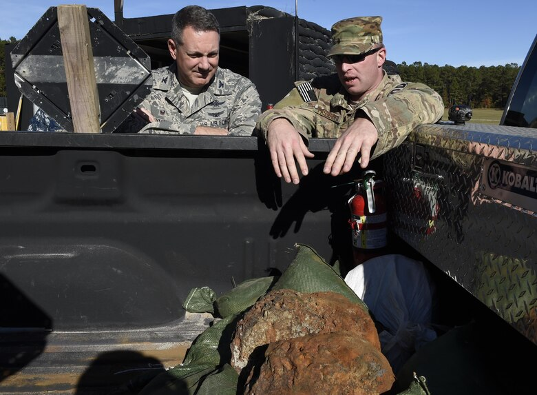 Master Sgt. Tracy Passerotti, 628th Civil Engineer Squadron, right, explosive ordnance disposal technician explains to JB Charleston commander Col. Robert Lyman, left, the background and procedures of proper disposal of Civil War-era explosives here. The 628th CES EOD flight worked with local emergency management teams to safely dispose of explosives brought ashore by the tides of Hurricane Matthew in October.