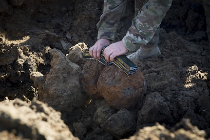 Senior Airman Dillon Babb, 628th Civil Engineer Squadron explosive ordnance disposal technician applies C4 explosive strips to Civil War-era cannonballs here. The 628th CES EOD flight worked with local emergency management teams to safely dispose of explosives brought ashore by the tides of Hurricane Matthew in October.