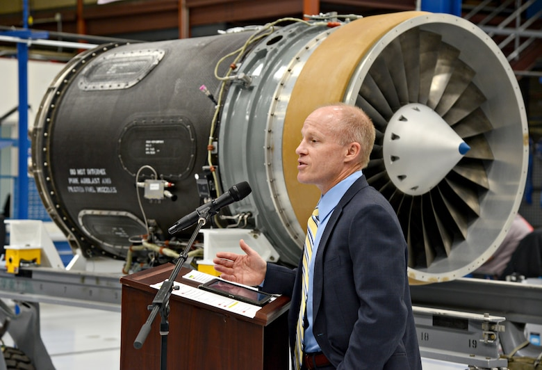 Phil Burkholder, president of Defense North America, Rolls-Royce, speaks on behalf of his company during the ribbon cutting ceremony for the new F137 engine maintenance line in Bldg. 3221. (Air Force photo by Kelly White)