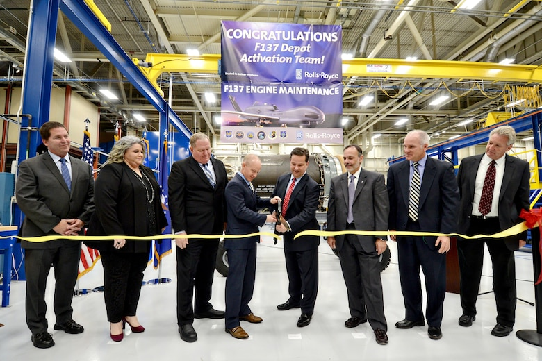 Phil Burkholder, president of Defense North America, Rolls-Royce, and Wade Wolfe, vice director of the Oklahoma City Air Logistics Complex, cut the ceremonial ribbon signifying the opening of the F137 engine maintenance line in Bldg. 3221 Nov. 15. Also present are three representatives with Rolls-Royce; Mr. Phil Burkholder, President, North America Rolls-Royce; Mr. Wade Wolfe, OC-ALC vice director; Ralph Garcia, director of Propulsion Directorate; Robert Helgeson, director of the 76th Propulsion Maintenance Group; and Mike Opela, director of the 544th Propulsion Maintenance Squadron. (Air Force photo by Kelly White)