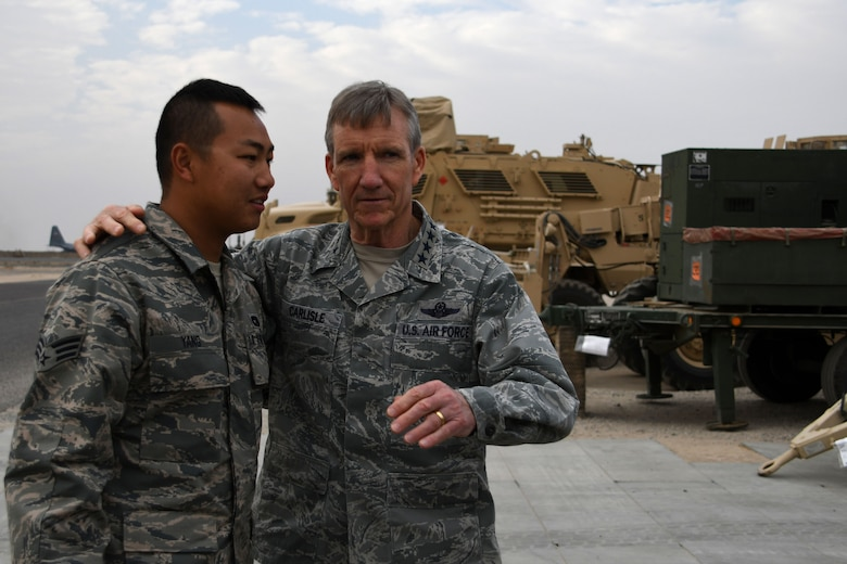 U.S. Air Force Gen. Hawk Carlisle, commander of Air Combat Command, shows his appreciation for Senior Airman Sang Yang, 386th Expeditionary Logistics Readiness Squadron air transportation journeyman, Nov. 23, 2016 at an undisclosed location in Southwest Asia. During his visit, Carlisle personally thanked Airmen across the wing for volunteering to serve their nation thousands of miles away from their families.  (U.S. Air Force photo/Senior Airman Andrew Park)