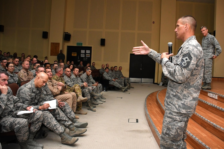Chief Master Sgt. Steve McDonald, command chief master sergeant of Air Combat Command, left, and U.S. Air Force Gen. Hawk Carlisle, commander of Air Combat Command, right, answer Airmen's questions during an All Call held Nov. 23, 2016 at an undisclosed location in Southwest Asia. McDonald and Carlisle addressed Airmen's concerns regarding subjects ranging from distance learning to enlisted pilot programs. (U.S. Air Force photo/Senior Airman Andrew Park)