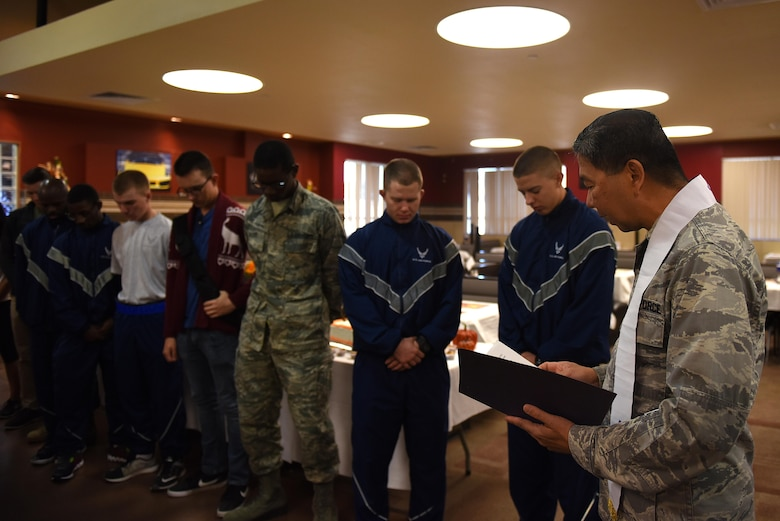 U.S. Air Force Chaplain (Capt.) Antonio Rigonan, 17th Training Wing, provides an opening prayer for Thanksgiving at the Cressman Dining Facility on Goodfellow Air Force Base, Texas, Nov. 24, 2016. Base leadership took turns serving service members, retirees and dependents for Thanksgiving. (U.S. Air Force photo by Airman 1st Class Caelynn Ferguson/Released)