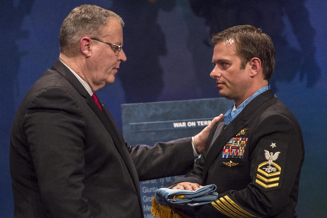 Deputy Defense Secretary Bob Work presents Navy Senior Chief Petty Officer Edward C. Byers Jr. the Medal of Honor flag during a ceremony to induct him into the Hall of Heroes at the Pentagon, March 1, 2016. DoD photo by Air Force Senior Master Sgt. Adrian Cadiz