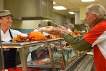 Senior Master Sgt. Tammy Moore, 4th Comptroller Squadron superintendent, hands a Red Cross volunteer a plate of food at the dining facility at Seymour Johnson Air Force Base, North Carolina, Nov. 24, 2016. Team Seymour leadership and 4th Force Support Squadron Airmen gave back to the Red Cross volunteers and staff members by providing a tour of the base and serving a hot Thanksgiving meal. (U.S. Air Force photo by Airman 1st Class Ashley Williamson)