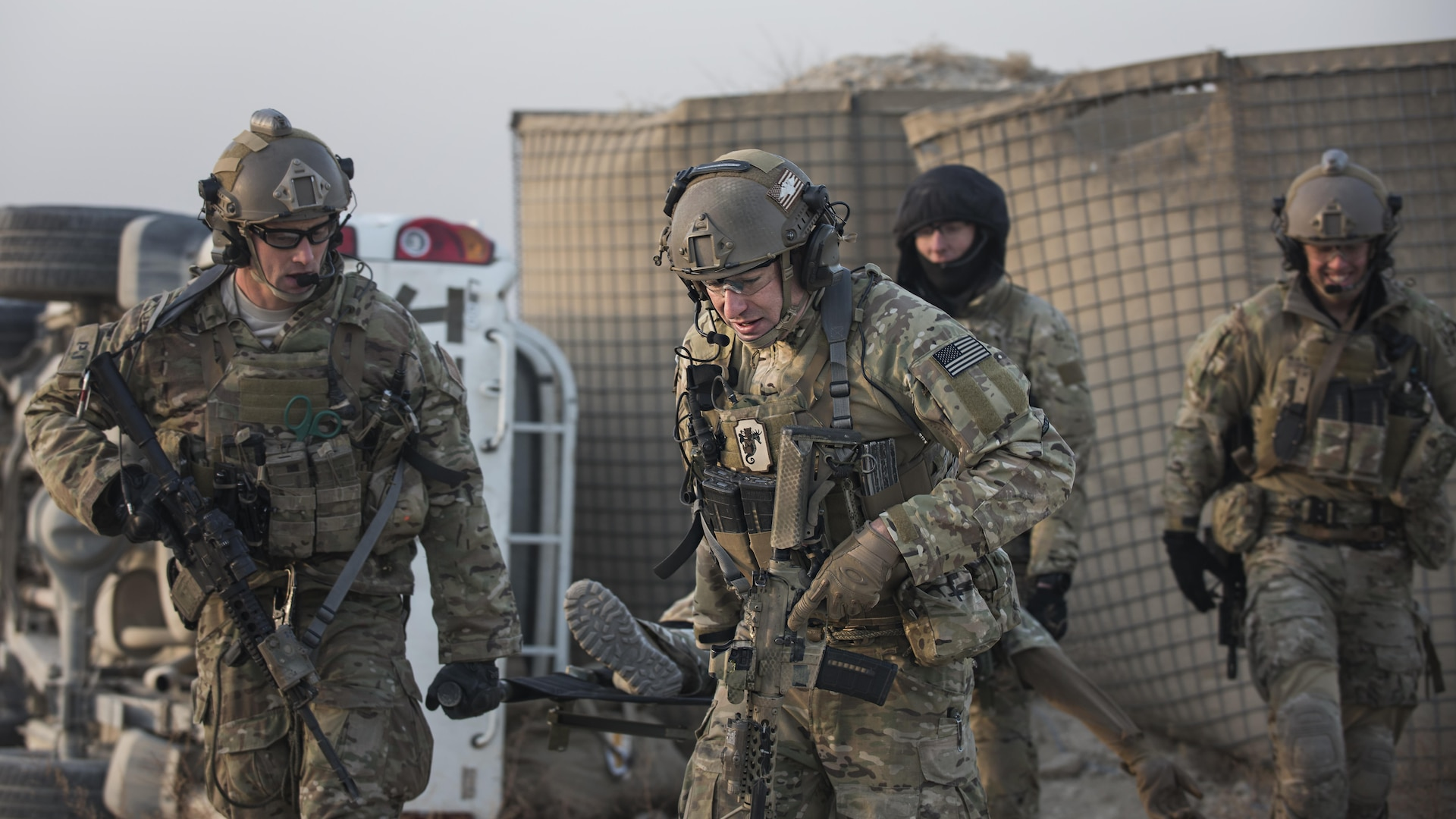 """""""Guardian Angels"""" of the 83rd Expeditionary Rescue Squadron carry a patient by litter for evacuation during a mass casualty exercise held Nov. 17, 2016 at Bagram Airfield, Afghanistan. Training scenarios are based on real-world situations that have been encountered in past operations. (U.S. Air Force photo by Staff Sgt. Katherine Spessa)"""