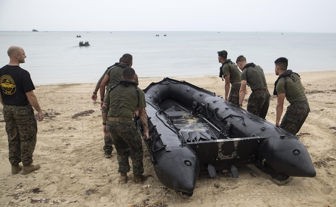 """Marines from 3d Reconnaissance Battalion, 3d Marine Division, III Marine Expeditionary Force, carry a rubber inflatable raft into the water to begin the """"boating"""" station on Camp Schwab, Okinawa, Japan, Nov. 23, 2016, during their annual Warrior Challenge. This event honors fallen Marines in the battalion and consists of nine stations to challenge the Marines mentally and physically. (U.S. Marine Corps photo by Lance Cpl. Andrew Neumann/Released)"""