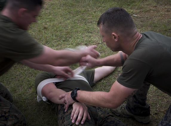 """Marines from 3d Reconnaissance Battalion, 3d Marine Division, III Marine Expeditionary Force, wrap a victim's arm during the """"medical"""" station on Camp Schwab, Okinawa, Japan, Nov. 23, 2016, during their annual Warrior Challenge. This event honors fallen Marines in the battalion and consists of nine stations to challenge the Marines mentally and physically. (U.S. Marine Corps photo by Lance Cpl. Andrew Neumann/Released)"""