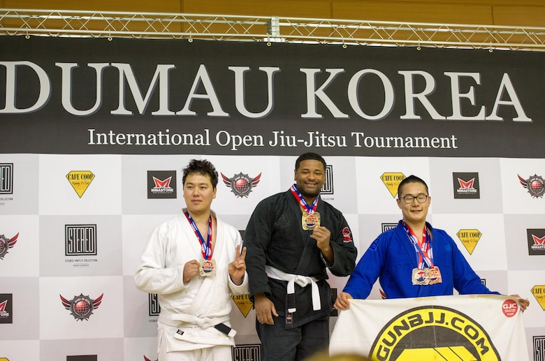 U.S. Air Force Staff Sgt. Brandon Davis (center), 51st Fighter Wing chaplain assistant, poses with his first place medal for master open weight white belt during the Dumau Jiu-Jitsu Korea Grand Prix 2016 in Seoul, Republic of Korea, Nov. 27, 2016. Davis won the master open weight white belt by beating 14 other competitors in a single-round eliminations competition. (U.S. Air Force photo by Staff Sgt. Jonathan Steffen)
