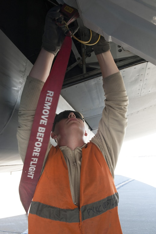U.S. Air Force Airman 1st Class Nathaniel, 447th Expeditionary Aircraft Maintenance Squadron crew chief, places safety pins in place on a KC-135 Stratotanker Nov. 2, 2016, at Incirlik Air Base, Turkey. Safety pins are used to lock points of the aircraft in place while on ground for safety. (U.S. Air Force photo by Staff Sgt. Jack Sanders)