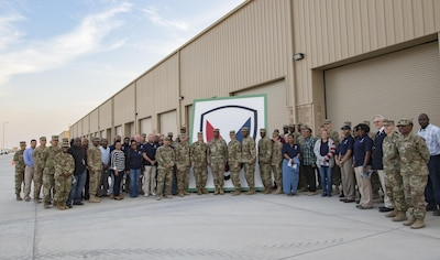 Service members and civilians gather for a group photo after a ribbon-cutting ceremony that celebrated the opening of several new equipment warehouses Nov. 17, 2016 at Camp Arifjan, Kuwait. The warehouses, designed and built by the U.S. Army engineers with the support of the Kuwait government, will store and protect Army equipment. (U.S. Army photo by Sgt. Angela Lorden)