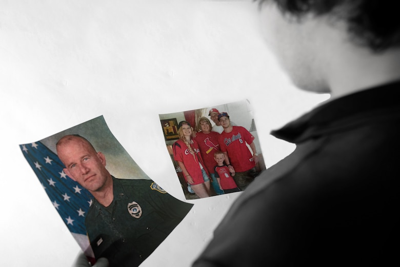Zach Donnelly, son of the late Dave Donnelly, holds photos of his father and his family at Ellsworth Air Force Base, S.D., Nov. 4, 2016. Donnelly's father passed away on Oct. 15 after a long battle with cancer. Prior to becoming a police officer with the Department of the Air Force, Dave served 10 years in the U.S. Army. (U.S. Air Force photo illustration by Airman 1st Class Denise M. Jenson)