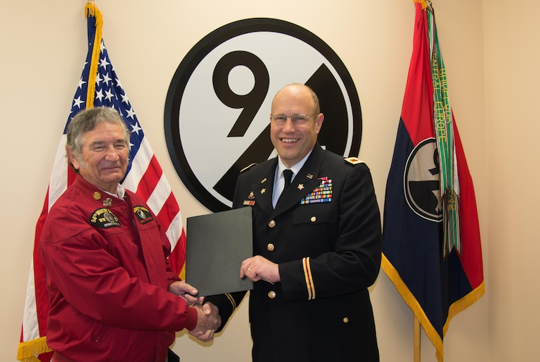 (Left) 94th Infantry Division Historical Society Secretary John Clyburn hands a Memorandum of Agreement to 94th Training Division Assistant Division Commander Col. John Aarsen at the division's headquarters at Fort Lee, Virginia, Nov. 21, 2016. According to the MOA, Aarsen promises the division will take good care of the society's flag. Clyburn took part in the flag transfer event, in which he and others from the society handed over their colors to Aarsen.