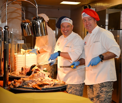 U.S. Air Force Brig. Gen. Mark Slocum, right, U.S. Air Forces in Europe-United Kingdom commander, and U.S. Air Force Col. Robert Hoskins, 100th Mission Support Group commander, pose for a photo as they serve turkey and ham Nov. 24, 2016, at the Gateway Dining Facility on RAF Mildenhall, England. The special meal was prepared in celebration of Thanksgiving and fed many Airmen and civilians from around Team Mildenhall. (U.S. Air Force photo by Karen Abeyasekere)