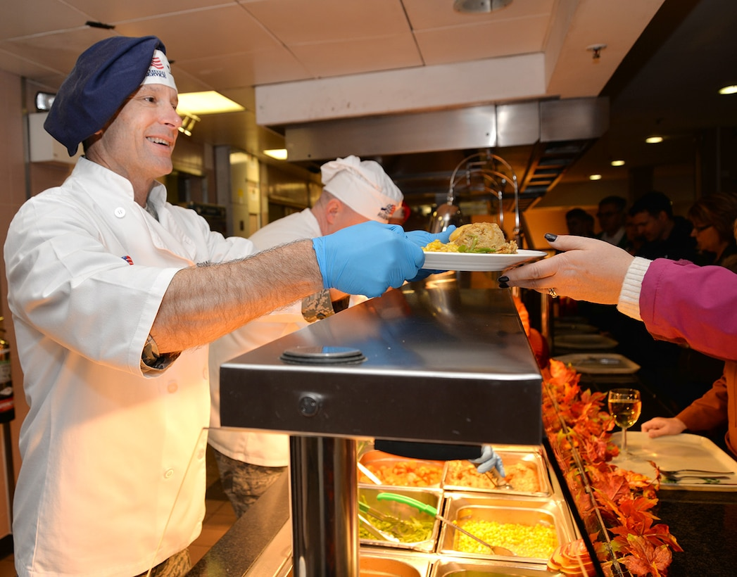 U.S. Air Force Col. Matthew Smith, left, 352nd Special Operations Wing commander, chats to a customer as he serves her food Nov. 24, 2016, at the Gateway Inn on RAF Mildenhall, England. The special meal was prepared in celebration of Thanksgiving and fed many Airmen and civilians from around Team Mildenhall. (U.S. Air Force photo by Karen Abeyasekere)