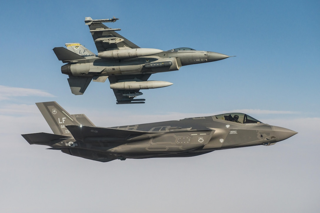 An F-35 Lightning II flies alongside an F-16 Fighting Falcon June 25, 2015, at Luke Air Force Base. In October, F-35 and F-16 pilots began integrated training designed to improve mission cooperation and flight skills in both airframes. (Courtesy Photo)