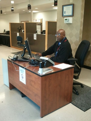 Defense Supply Center Richmond Welcome Center receptionist Michael Abraham readies to receive the next customer and issue a ticket using the new Visitor Management System.
