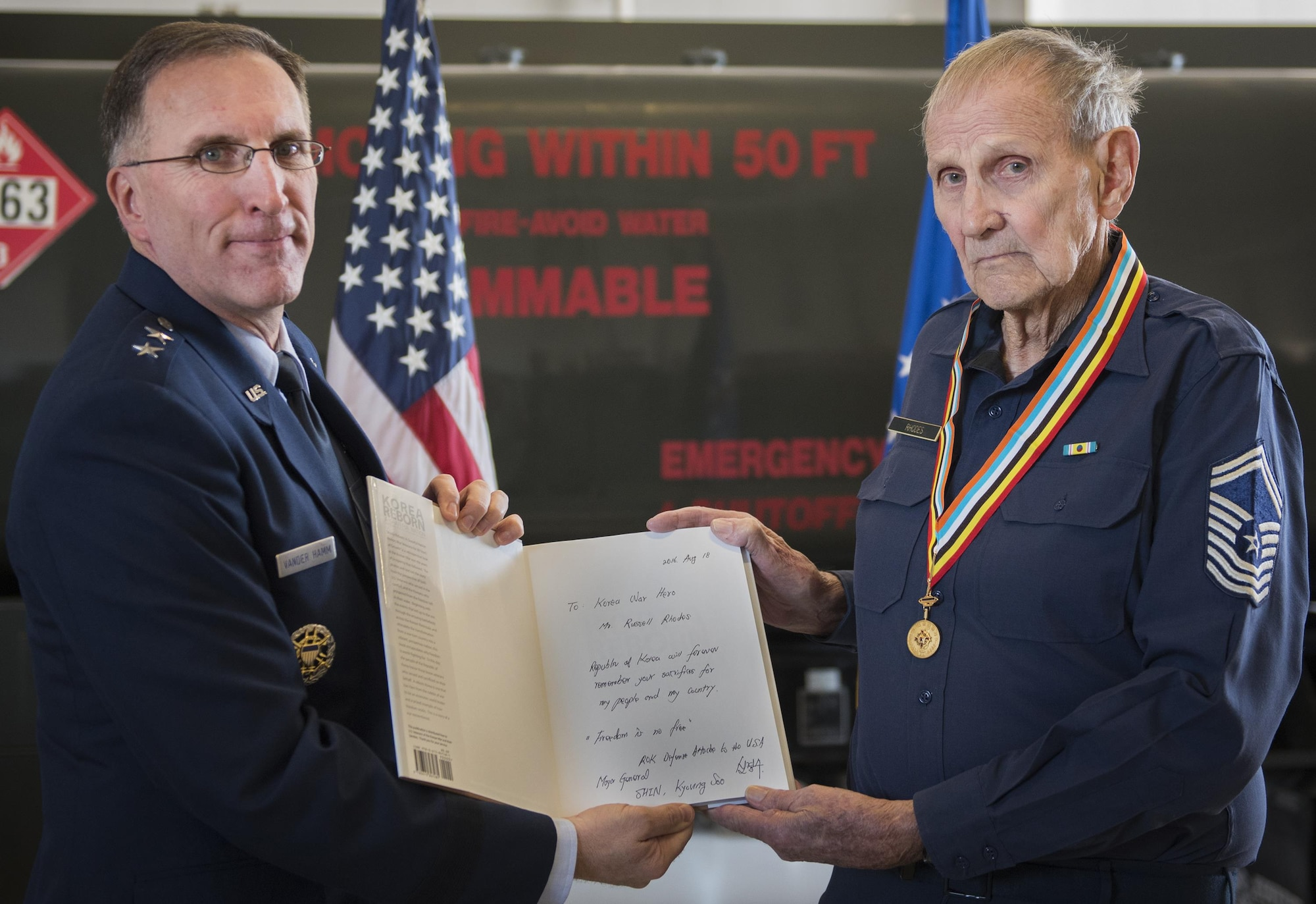 Maj. Gen. Scott Vander Hamm, the Air Force assistant deputy chief of staff of operations, holds a signed book with his uncle, retired Chief Master Sgt. Russell Rhodes, after presenting him with the Korean Ambassador for Peace Medal during a ceremony held at Eglin Air Force Base, Fla., Nov. 15, 2016. The 85-year-old Rhodes requested the medal ceremony be held at the base's fuels flight, where Rhodes was stationed during his Air Force career as a fuel truck driver. (U.S. Air Force photo/Samuel King Jr.)