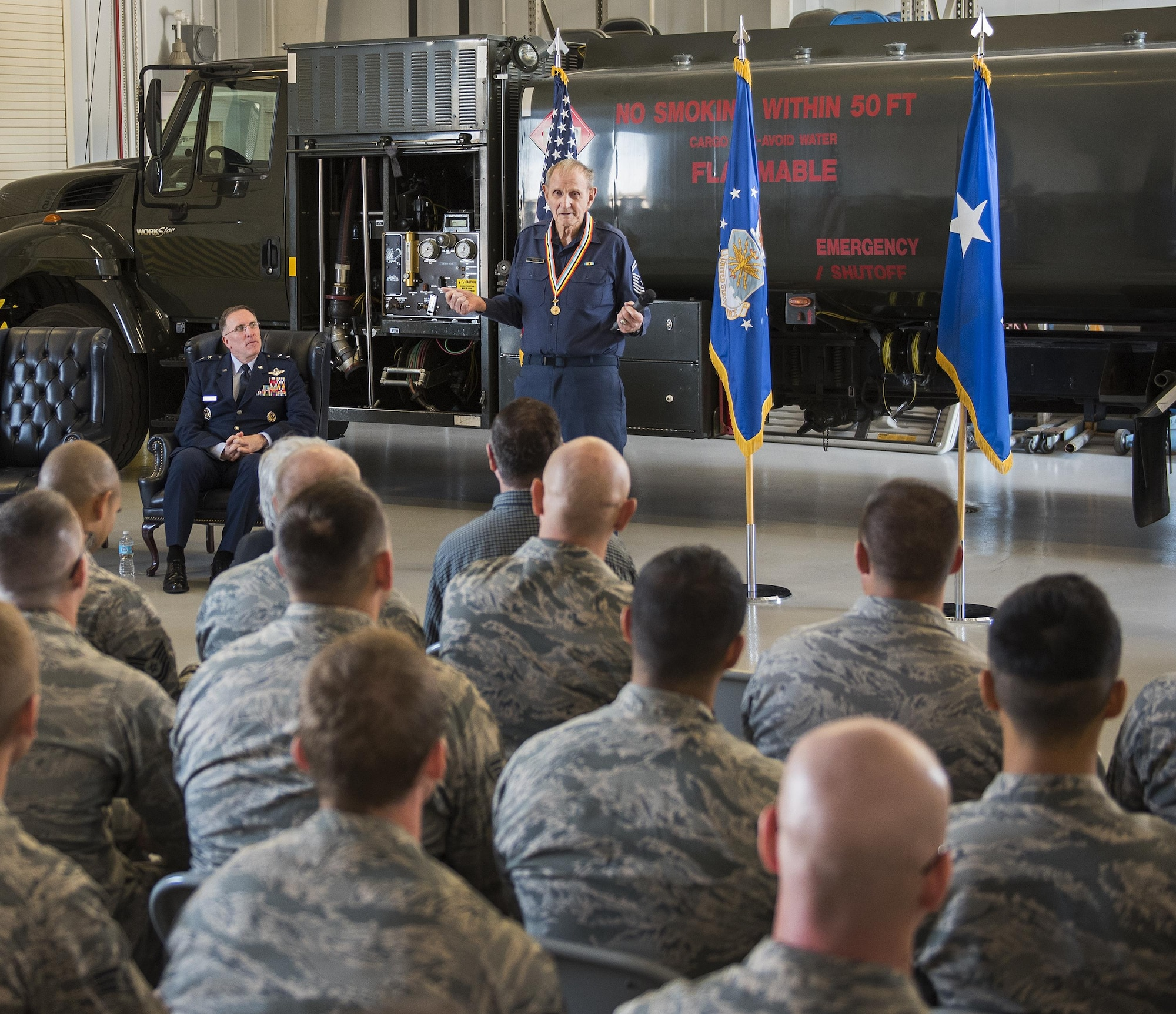 Retired Chief Master Sgt. Russell Rhodes speaks to an audience after receiving the Korean Ambassador for Peace Medal at Eglin Air Force Base, Fla., Nov. 15, 2016. The 85-year-old Rhodes requested the medal ceremony be held at the base's fuels flight, where Rhodes was stationed during his Air Force career as a fuel truck driver. (U.S. Air Force photo/Samuel King Jr.)