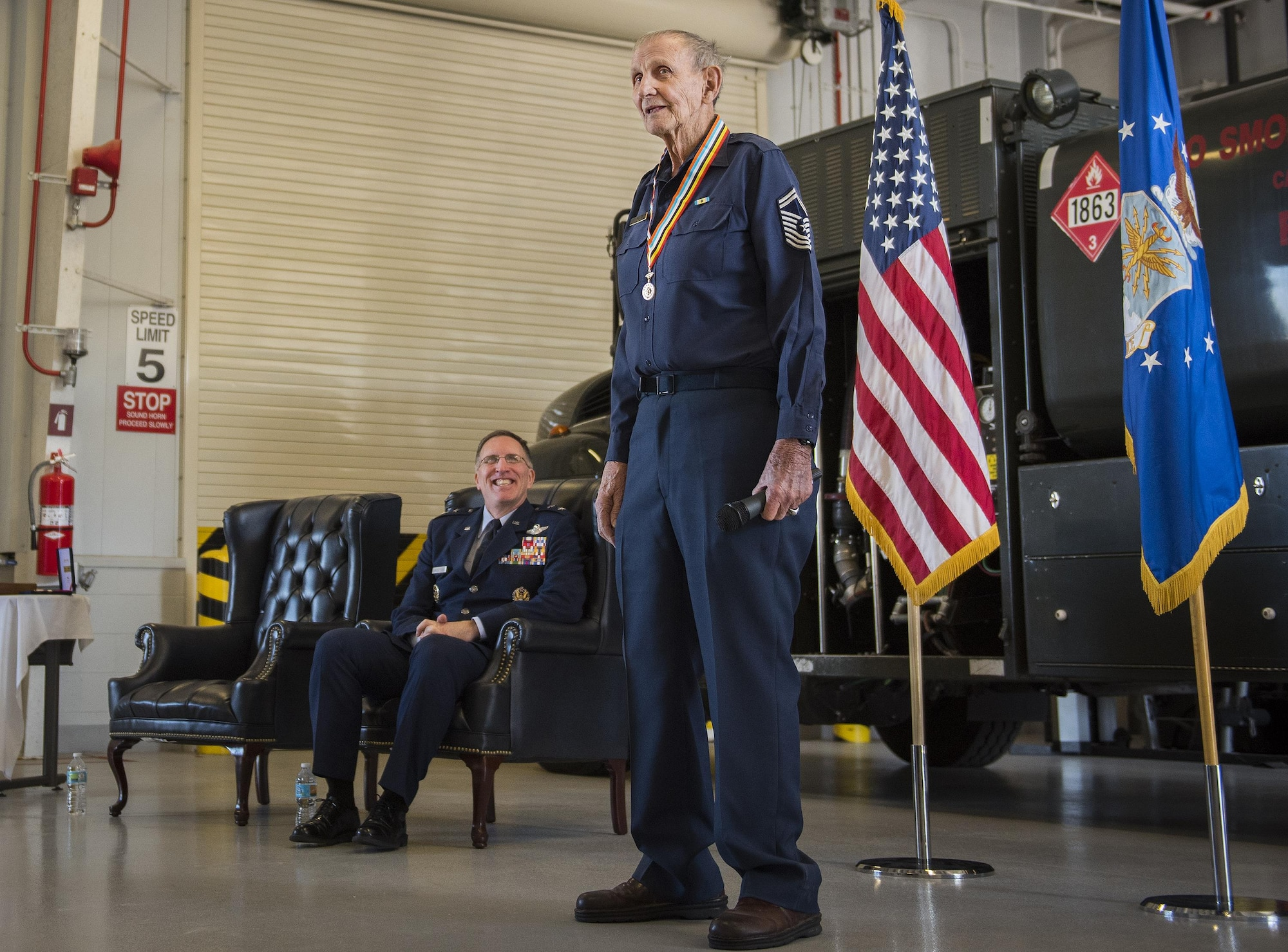Retired Chief Master Sgt. Russell Rhodes speaks to the audience after receiving the Korean Ambassador for Peace Medal at Eglin Air Force Base, Fla., Nov. 15, 2016. The 85-year-old Rhodes requested the medal ceremony be held at the base's fuels flight, where Rhodes was stationed during his Air Force career as a fuel truck driver. (U.S. Air Force photo/Samuel King Jr.)
