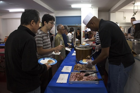 Service members from Camp Kinser serve a special Thanksgiving meal to Okinawa residents at the Promise Keepers Homeless Shelter Nov. 24 in Urasoe City, Okinawa, Japan. The event provided service members with the opportunity to positively impact the Okinawa community through food, fellowship and holiday celebration. During the dinner, Okinawan patrons and service members enjoyed a traditional Thanksgiving meal together. (U.S. Marine Corps photo by Cpl. Janessa K. Pon)