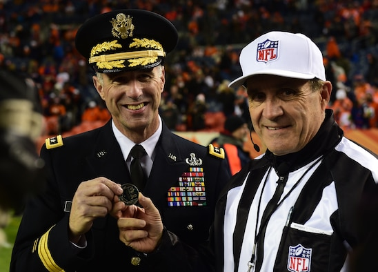 U.S. Army Maj. Gen. Reynold N. Hoover, Mobilization Assistant to the Director, Defense Intelligence Agency, presents a game official with a coin before a Denver Broncos Salute to Service pregame ceremony Nov. 27, 2016, at Sports Authority Field at Mile High in Denver. The Salute to Service program is a way the NFL thanks military members for their service. (U.S. Air Force photo by Airman 1st Class Gabrielle Spradling/Released)
