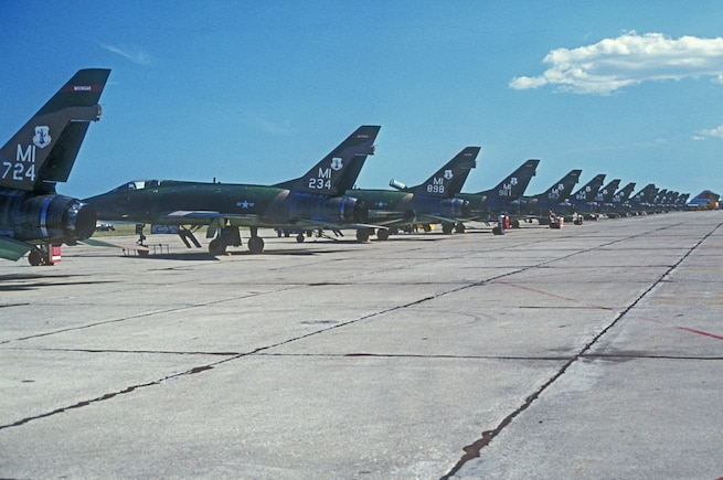 F-100 Super Sabres line the ramp at Selfridge Air National Guard Base, Mich., in the middle 1970s. The F-100, shown here sporting the tail flash of the Michigan Air National Guard, was an air superiority aircraft capable of supersonic flight. It was flown by the 107th Fighter Squadron at Selfridge. (Michigan Air National Guard photo)