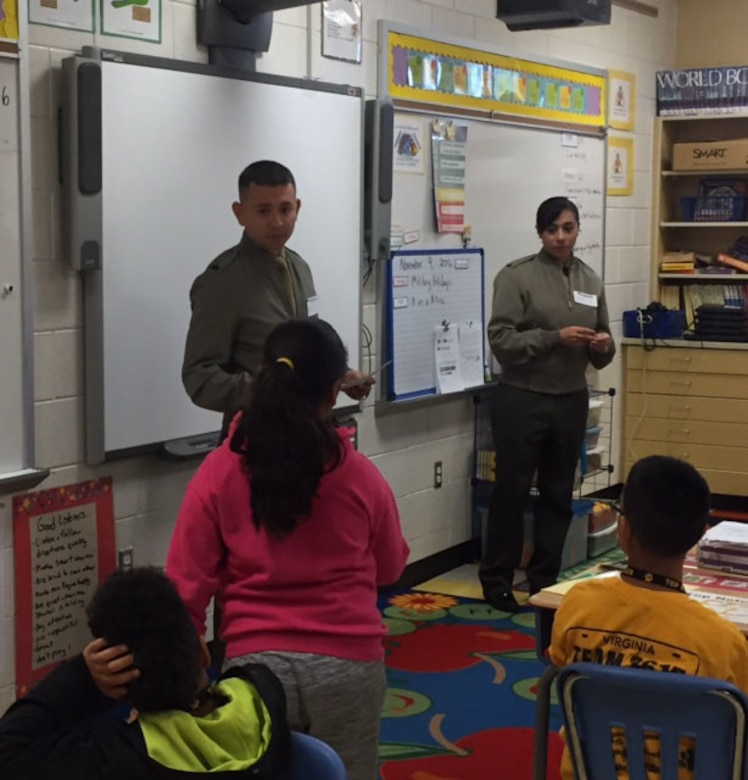 On 9 November, sixteen Marines visited Triangle Elementary School in Prince William County outside the main gate of Quantico as part of the Adopt-A-School program. Once the Marines arrived at the school, they greeted students and helped them with their morning routine.  During the day, Marines participated in activities in all grade levels at the school.  Marines demonstrated how to do a proper push up as part of wellness stations in PE, helped Head Start students open their milk for breakfast, read to kindergartners, and presented good behavior certificates to 3rd graders.     Triangle Elementary is just one of the schools that benefit from the program, which sends Marines to public schools to assist teachers and students and ultimately have a positive impact on the lives of students.