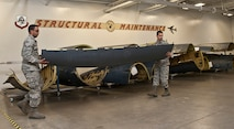 (From left) Senior Airmen Mikal Joyce and Jan Nazario, 5th Maintenance Squadron aircraft structural maintenance journeymen, carry a cowling at Minot Air Force Base, N.D. Oct. 27, 2016. These Airmen use various methods like sanding, corrosion and tubing to either build or install replacement parts for an aircraft. (U.S. Air Force photo/Airman 1st Class Jonathan McElderry)