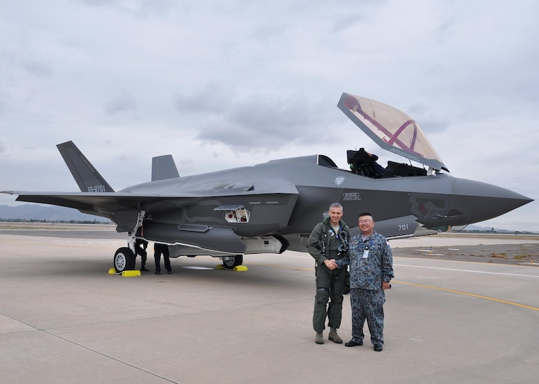 Maj. Toru Tsuchiya, Japan Air Self-Defense Force, Japanese F-35A foreign liaison officer and Lt. Col. Todd Lafortune, Defense Contract Management Agency Lockheed Martin, F-35 acceptance pilot, shake hands Nov. 28 during the arrival of the first Foreign Military Sales F-35 at Luke Air Force Base, Ariz. (U.S. Air Force photo by Tech. Sgt. Louis Vega Jr.)