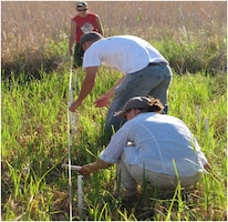 Biologist Kathleen Buckler (front) installs markers for a sampling area.