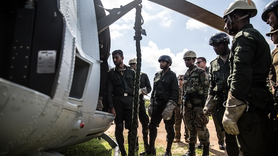 TRINCOMALEE, Sri Lanka (Nov. 23, 2016) Sri Lankan Navy Special Boat Squadron Sailors are instructed how to safely maneuver through the UH-1Y Huey helicopter during a Theater Security Cooperation engagement at Sri Lanka Naval Base, Trincomalee, Nov. 23, 2016. A majority of the SBS Sailors has never conducted fast rope techniques from an actual helicopter, so understanding the safety procedures and familiarizing themselves with the Huey prior to loading the aircraft was critical to the training event and everyone's safety. This bilateral training provides an opportunity for Sri
