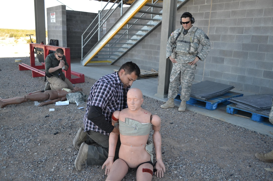 Sgt. Cesar Medina, front, and Sgt. Ryan Hernandez, back, Company B, 410th Civil Affairs Battalion, U.S. Army Reserve, work on simulated casualties during close-quarters combat training at McGregor Range, N.M., Nov. 19, 2016. First Lt. Colby Richardson, in uniform, team chief and officer in charge of the range, evaluates.